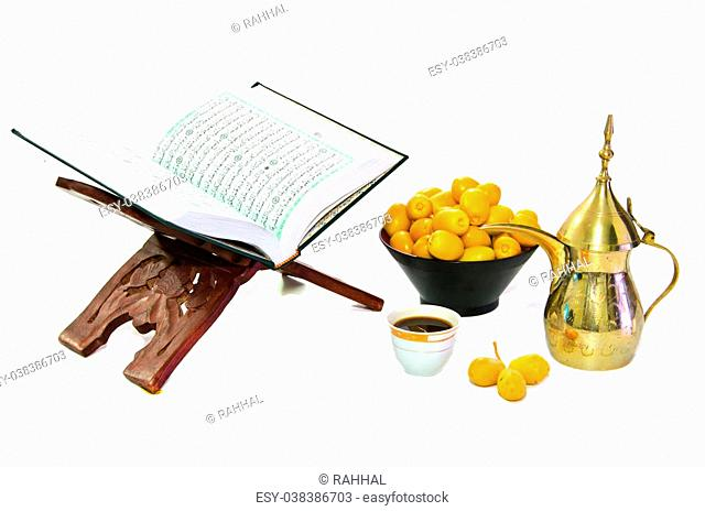 The Holy Quran and Arabic Coffee with date fruit on white background