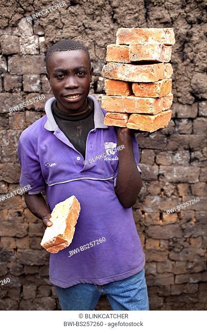 worker standing with clay bricks in front of mud wall, Burundi, Karuzi, Buhiga