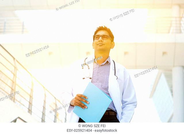 Portrait of Asian Indian medical doctor standing outside hospital building, beautiful golden sunlight at background