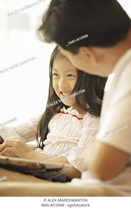 Father and daughter, sitting side by side, book between them