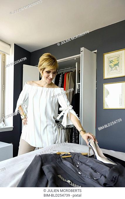 Caucasian woman preparing outfit on bed