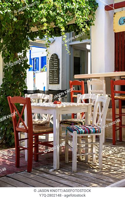 Shaded cafe scene of table and chairs in Kamares Town, Sifnos, Cyclades, Greece