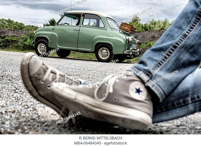 legs with sneakers in front of a Goggomobil