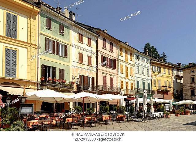 outdoor cafes and old picturesque buildings on Motta square at historical touristic village, shot on bright summer day at Orta San Giulio, Novara, Cusio, Italy