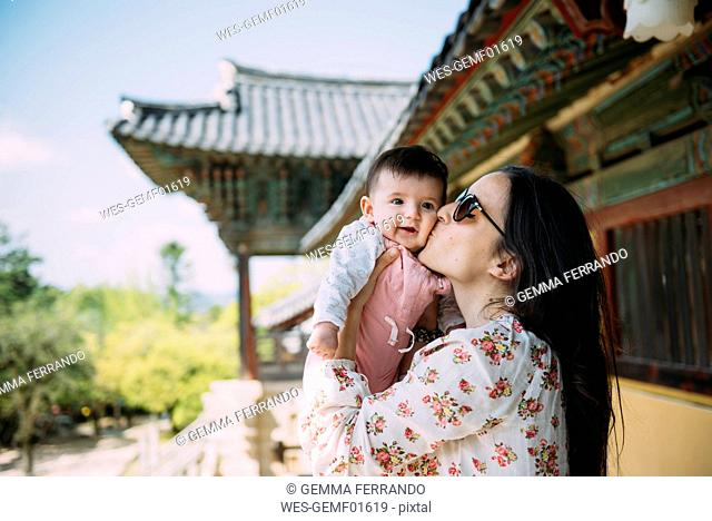 South Korea, Gyeongju, womankissing a baby girl in Bulguksa Temple