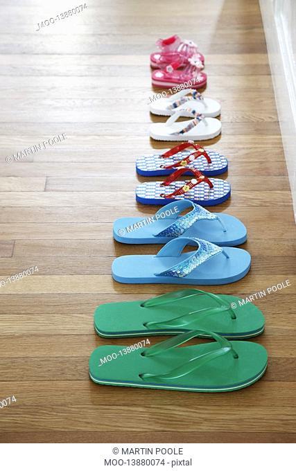 Row of flip-flops on floor elevated view