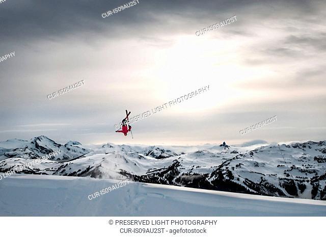 Skier doing backflip on natural wind-lip, Whistler Blackcomb, British Columbia, Canada
