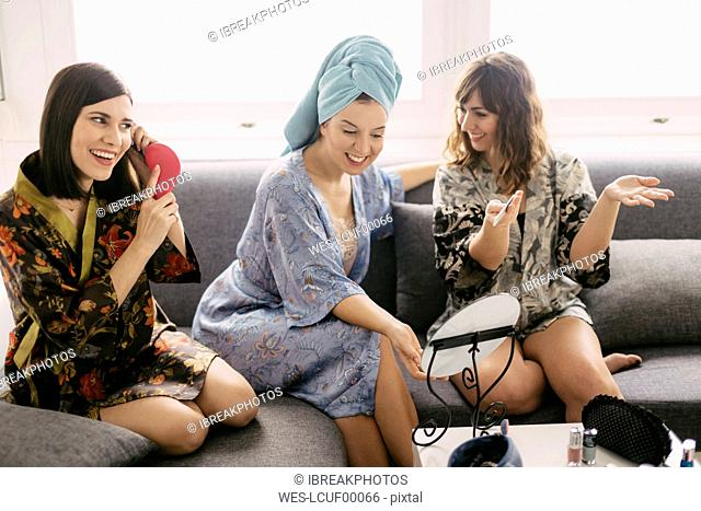 Three young women sitting on the couch wearing bathrobes preparing for the day