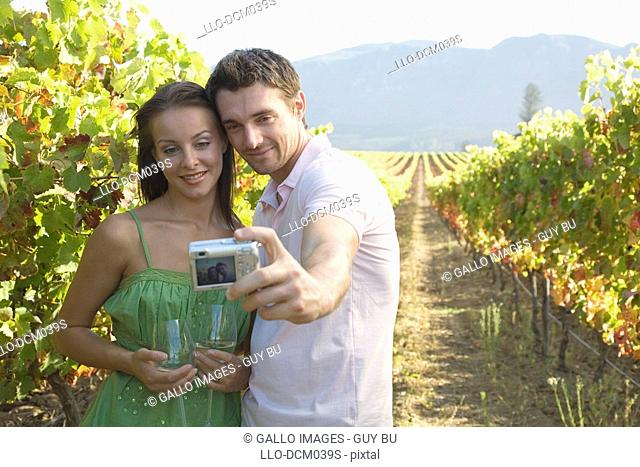 Young couple taking a self photograph in the grapevines in Cape Town, Western Cape Province, South Africa