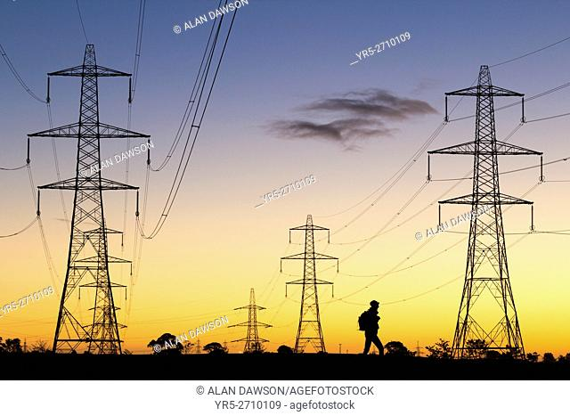 Hiker walking under power lines in pre dawn light in Cowpen Woodland Park near Billingham, north east England, United Kingdom