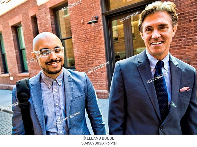Two businessmen walking together in street, smiling