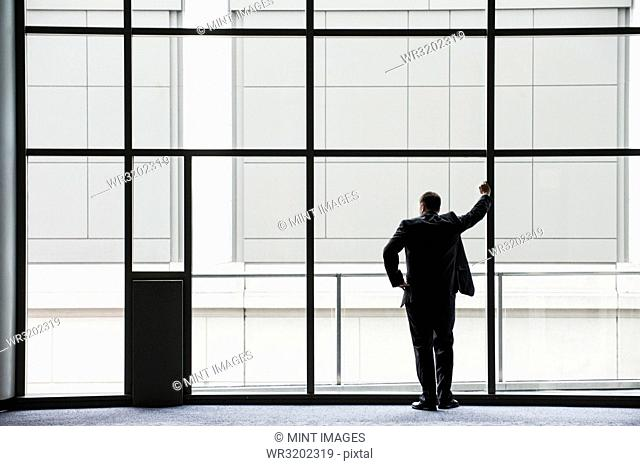 A businessman in silhouette standing at a large window in a convention centre lobby