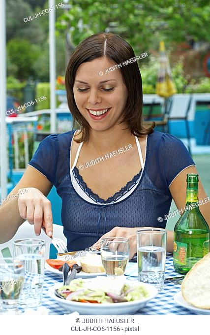 Young woman on table in Greek tavern in front of plates slicing her food happy