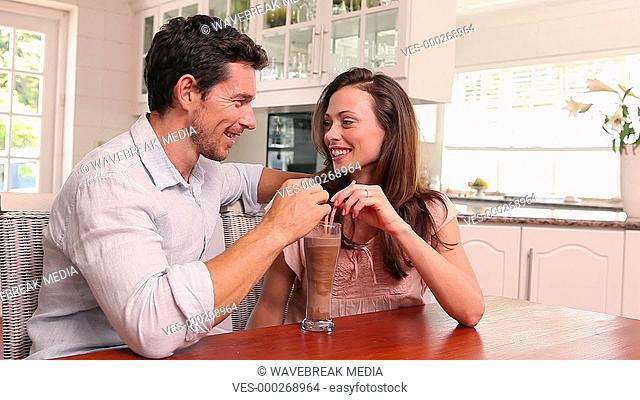 Happy couple drinking a milkshake together