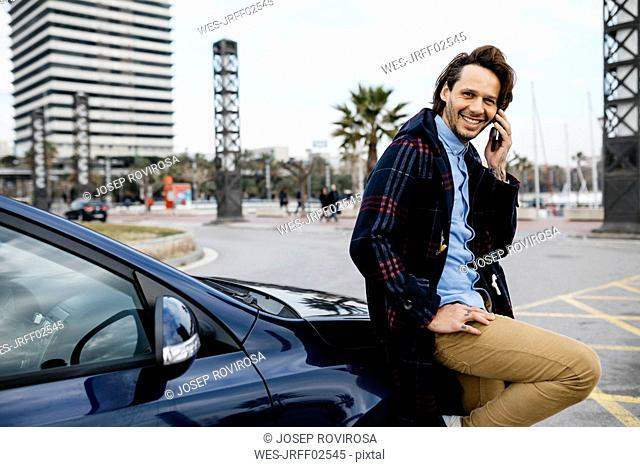 Spain, Barcelona, smiling man on cell phone outside car in the city