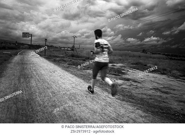 Man running with storm clouds in background. Alcocebre, Valencian Community, Spain