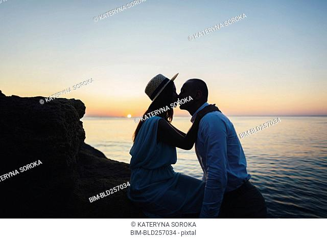 Caucasian couple kissing on rock near ocean at sunset