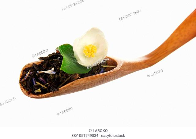 Fragrant tea leaves with cornflower and jasmine flower in a wooden spoon isolated on white background