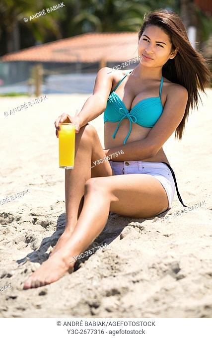 Young attractive woman with organge beverage sitting at the beach