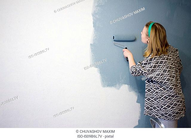 Young woman on step ladder applying grey paint to interior wall at home