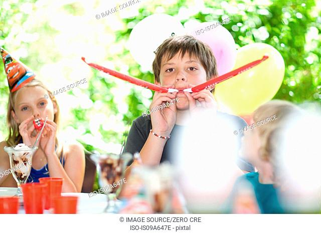 Children blowing noisemakers at party