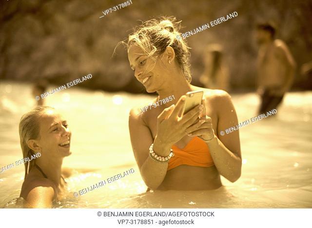 two women in sea water, bikini, using smartphone, at Seitan Limania Beach, Crete, Greece