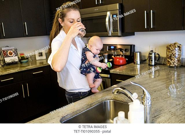 Mother drinking water while holding baby daughter (2-5 months)