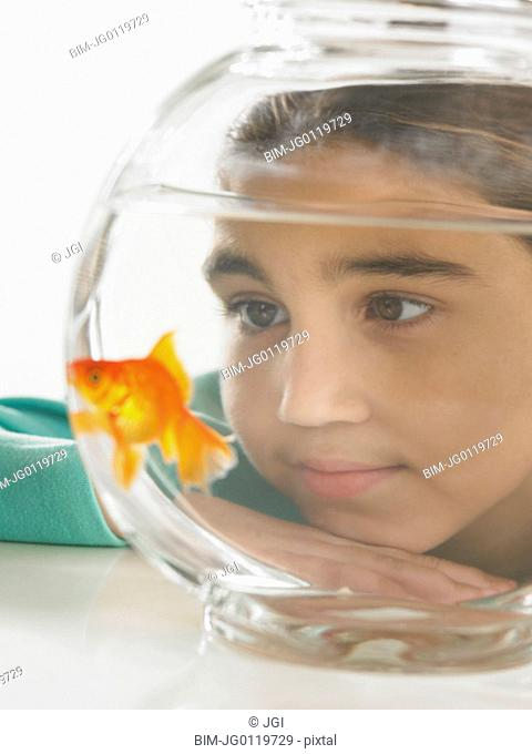 Young girl watching a goldfish in a fishbowl