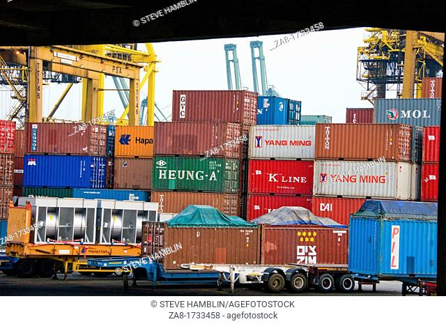 Stacks of large overseas shipping containers waiting to be loaded on boats