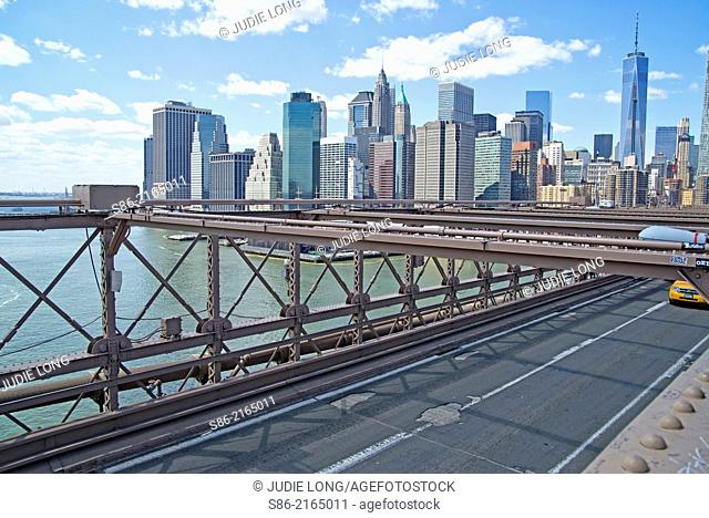 Looking at the Lower Manhattan Financial District Skyline from the Brooklyn Bridge, Traffic Lane Visible, Cab Entering the Frame, New York City, USA