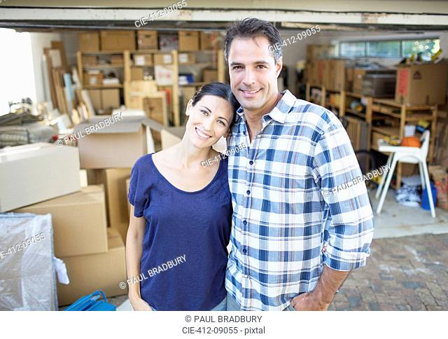 Portrait of smiling couple outside garage among cardboard boxes