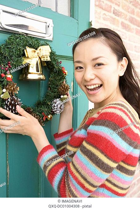 A woman decorating Christmas wreath
