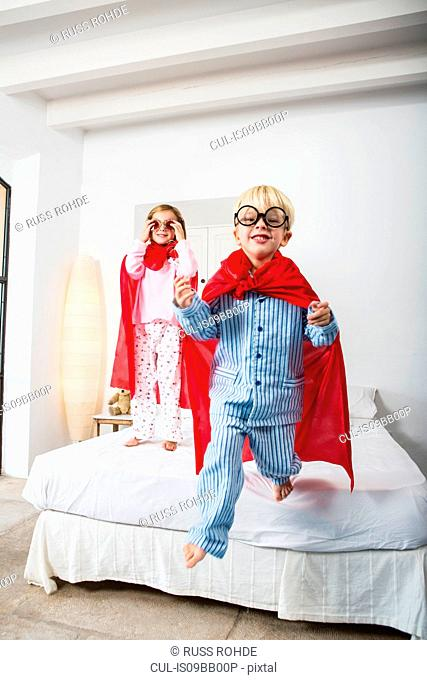 Boy and female twin in red capes jumping from bed