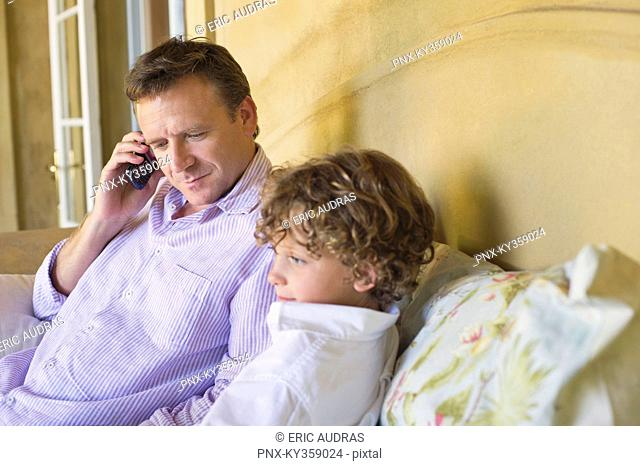 Father talking over mobile phone with little boy sitting with him on couch