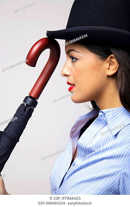 Businesswoman in bowler hat with umbrella