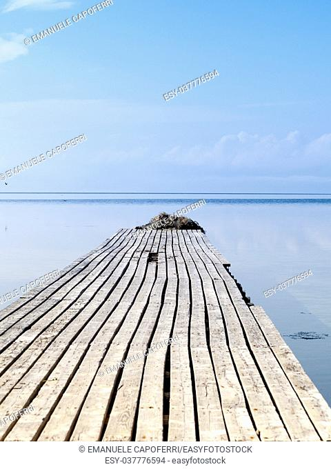 Djerba, Tunisia, wooden jetty with old axes converging towards infinity and horizon in the sea