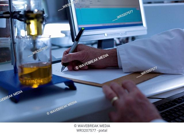 Male scientist writing on clipboard in laboratory