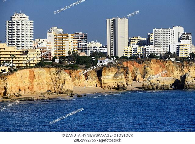 Praia do Vau, Praia dos Careanos and Praia dos Três Castelos, on cliffs above beaches modern apartment buildings and hotels, view of coast in Portimão, Algarve