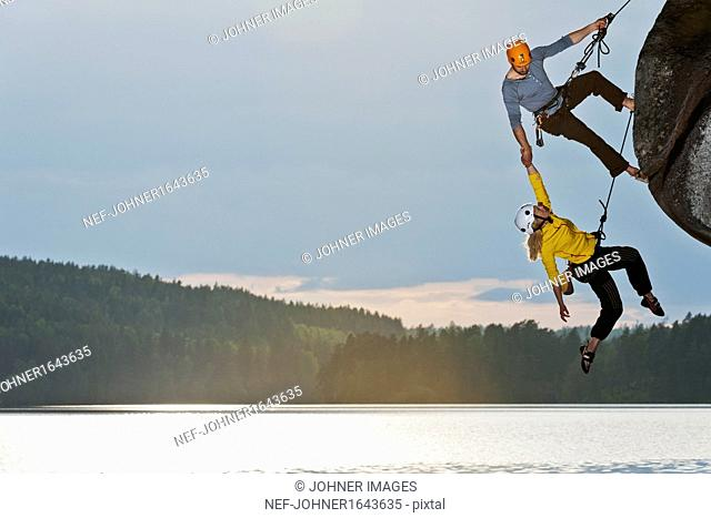 Woman and man climbing cliff