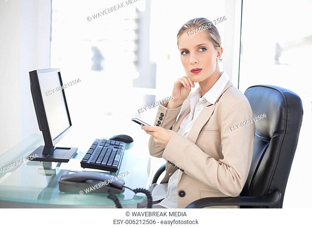 Thoughtful blonde businesswoman texting