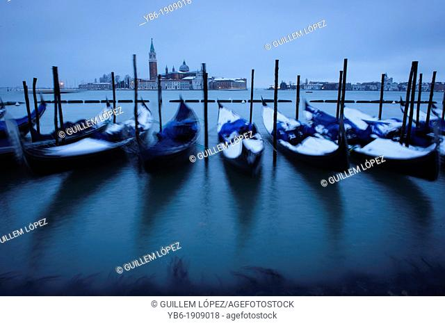 Snow covered gondolas seen at Venice's waterfront during the heavy snowfall and severe weather in Venice