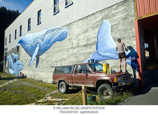 "Artist Justine Pechuzal painting her mural """"Sea-ward Bound"""" depicting humpback whales (Megaptera novaeangliae) on a wall facing the Alaska Sea Life Center"
