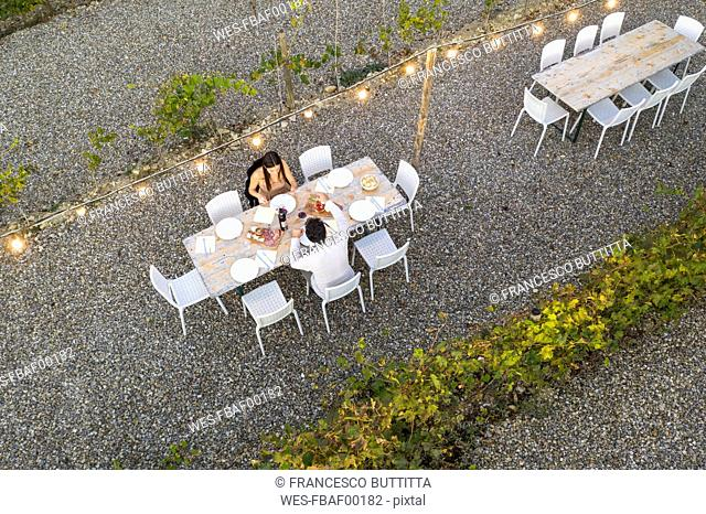 Italy, Tuscany, Siena, top view of young couple having dinner in a vineyard