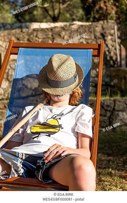 Greece, Corfu, boy with hat in deckchair