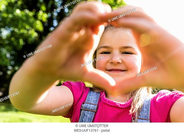 Portrait of smiling girl shaping a heart with her hands in park