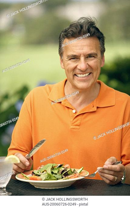 Portrait of a mature man sitting at the table with a plate of vegetable salad in front of him