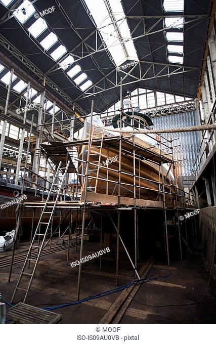 Scaffolding and boat in shipyard workshop