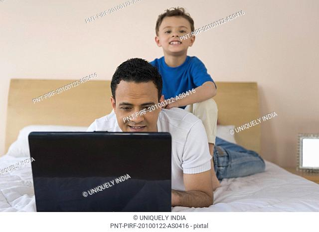 Man using a laptop with son sitting on his back
