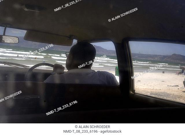 Rear view of a man sitting in a car on the beach, Muizenberg Zonwabe Beach, Muizenberg, False Bay, Cape Town, Western Cape Province, South Africa