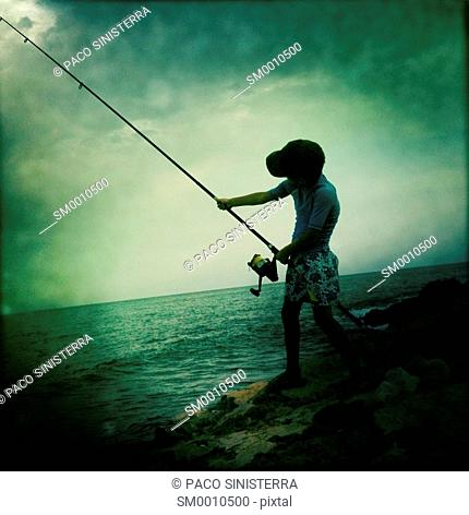 Silhouette of boy fishing in Denia, Alicante, Spain
